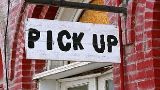 White sign reading pick up in black lettering hanging over a door
